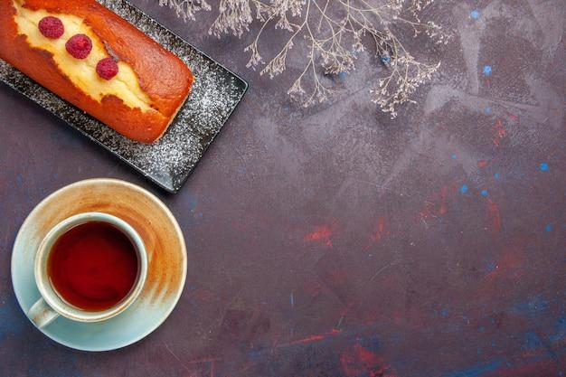 Draufsicht leckerer kuchen mit tasse tee auf dunklem oberflächenkuchen zuckerplätzchenkuchen süßer kekstee