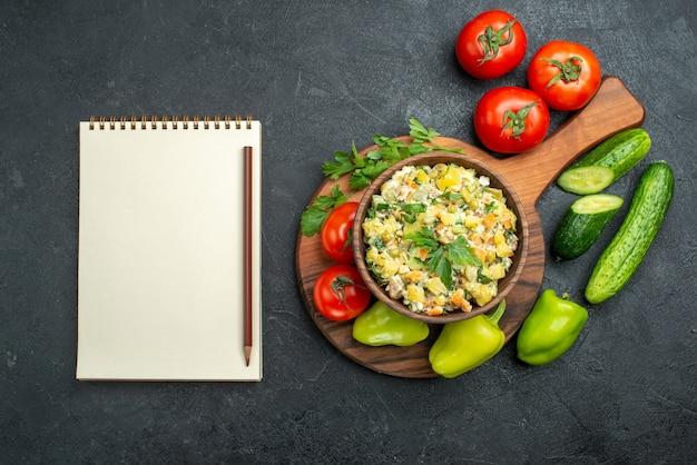 Draufsicht leckerer mayonaonaise-salat mit frischem gemüse und notizblock auf grau