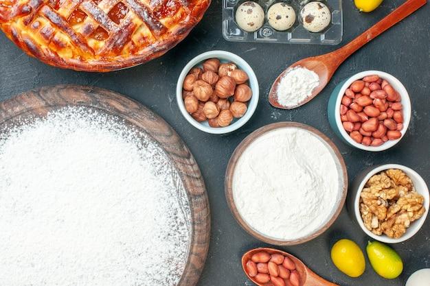 Draufsicht leckerer obstkuchen mit marmelade und mehl auf dem dunklen dessertkuchen süßer teekuchen teig keks backen zucker