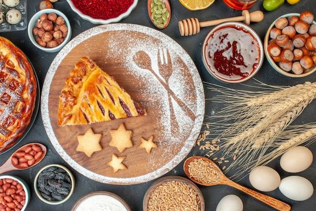 Draufsicht leckerer obstkuchen mit marmeladennüssen und mehl auf dem dunklen keks dessertkuchen teekuchenteig süßer backzucker