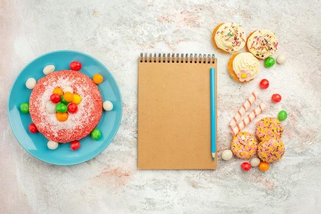 Draufsicht leckerer rosa kuchen mit leckeren kekskuchen auf weißer oberfläche goodie rainbow candy dessert farbkuchen