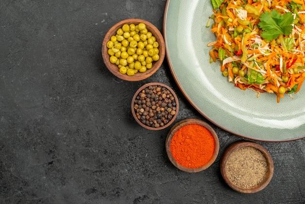 Draufsicht leckerer salat mit gewürzen auf der grauen salatlebensmittel-gesundheitsdiät