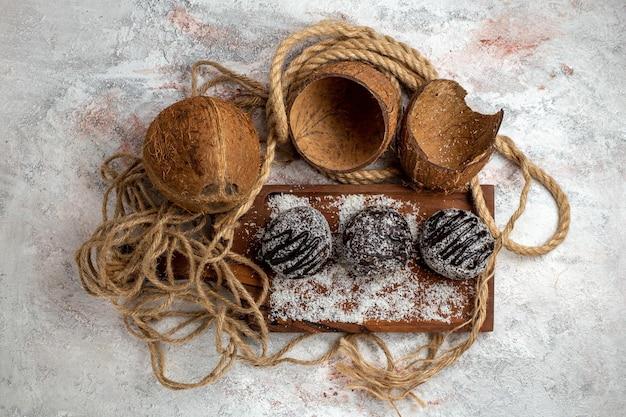 Draufsicht leckerer schokoladenkuchen mit kokos auf der hellweißen oberfläche
