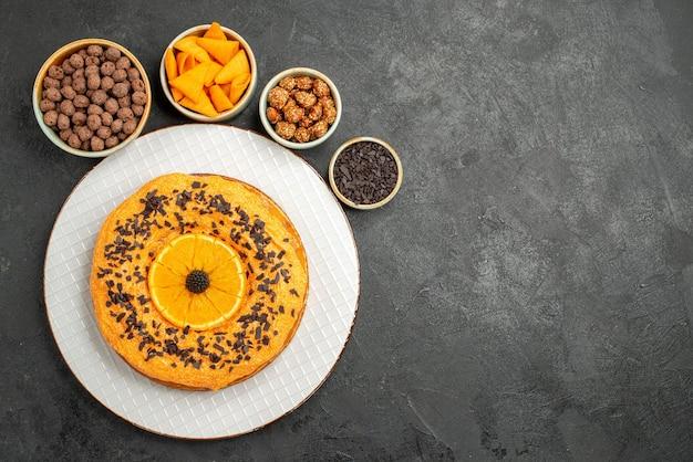 Draufsicht leckerer süßer kuchen mit orangenscheiben auf dem grauen oberflächenkeksdessert süßer kuchenkuchentee