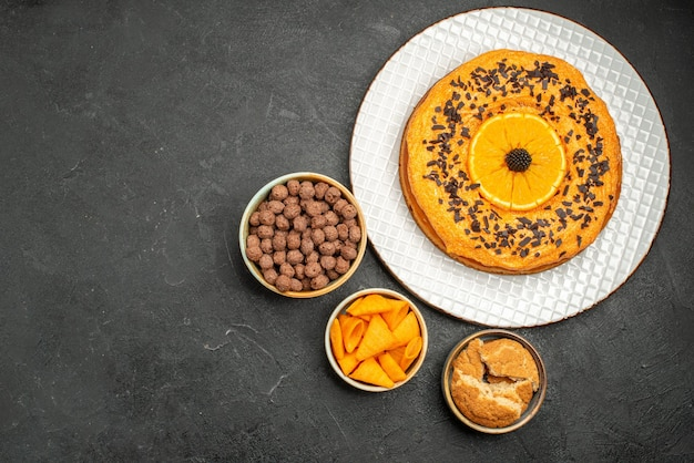 Draufsicht leckerer süßer kuchen mit orangenscheiben auf dunkelgrauem schreibtisch süßer kuchen dessert tee keks kuchen zucker
