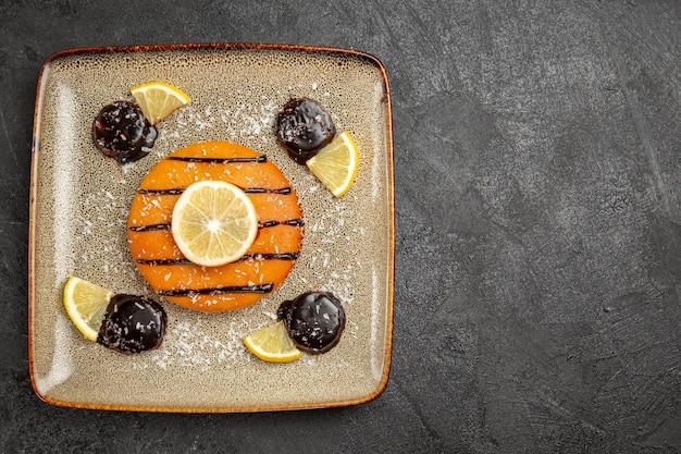 Draufsicht leckerer süßer kuchen mit schokoladensauce und zitronenscheiben auf dunkelgrauem hintergrund kuchenkuchen keks teig süßer keks