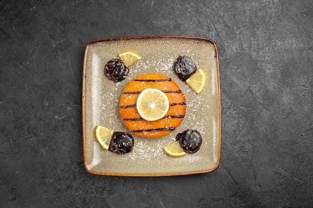 Draufsicht leckerer süßer kuchen mit schokoladensauce und zitronenscheiben auf grauem hintergrund kuchenkuchen keks teig süße kekse