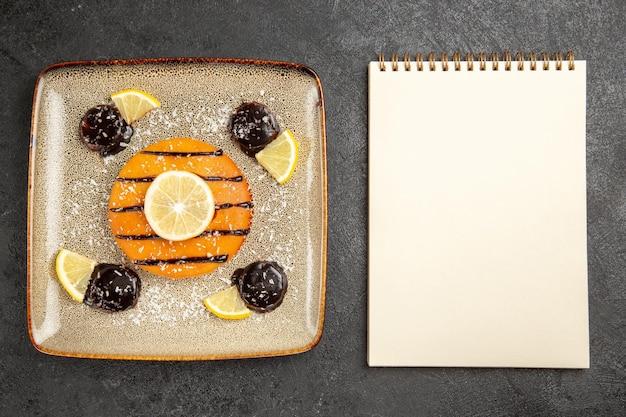 Draufsicht leckerer süßer kuchen mit schokoladensauce und zitronenscheiben auf grauem schreibtischkuchenkuchen keksteig süßer keks