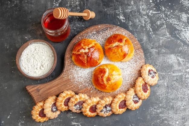 Draufsicht leckeres abendessen brötchen auf holz servierbrett kekse mit marmelade honigmehl auf dunklem tisch