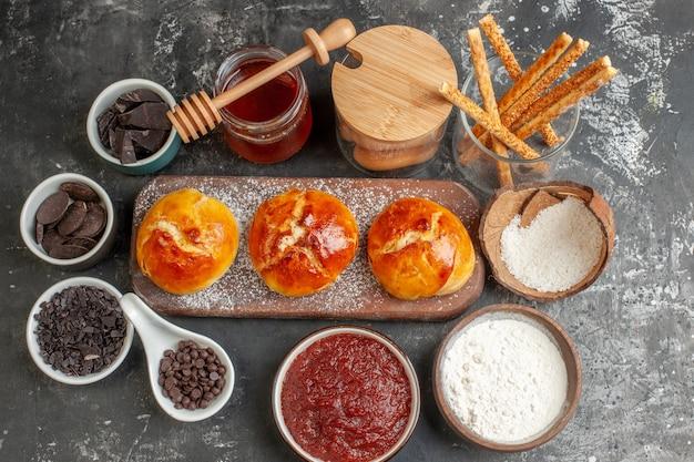 Draufsicht leckeres abendessen brötchen auf holzbrett mehl in holzschale marmelade schokolade in kleinen schalen honig auf dunkel