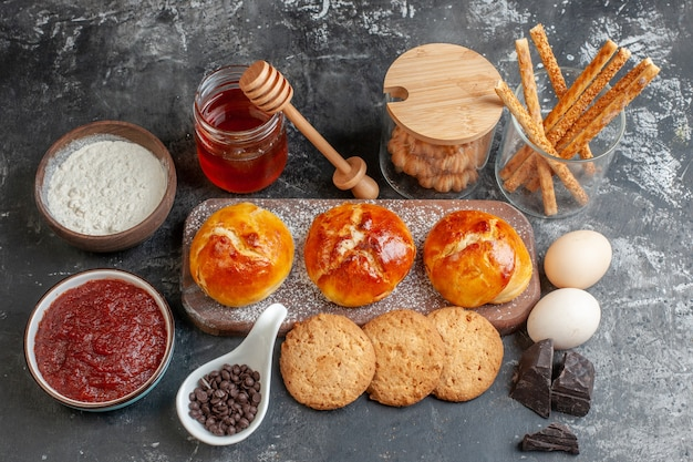 Draufsicht leckeres abendessen brötchen auf holzbrett mehl in holzschale marmelade schokolade in kleinen schalen kekse honig auf dunkel