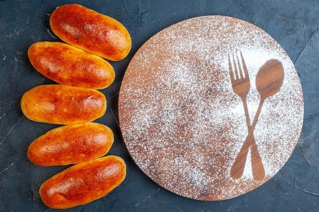 Draufsicht leckeres abendessen brötchen gabel und löffel aufdruck in puderzucker auf rundem holzbrett auf dem tisch