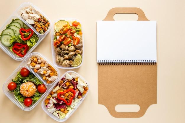 Draufsicht leckeres batch-essen mit leerem notizbuch gekocht
