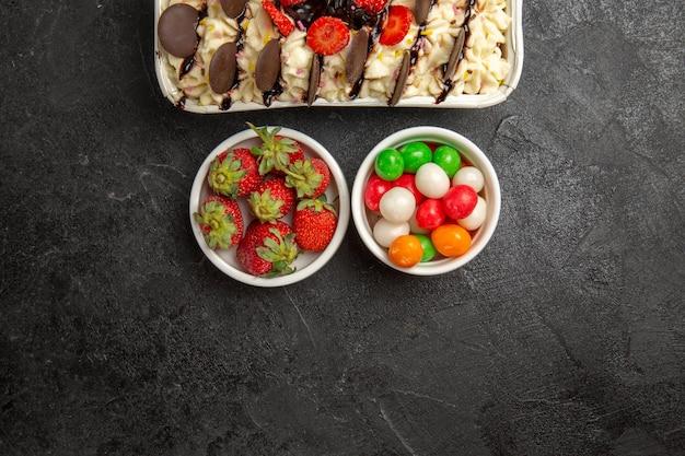 Draufsicht leckeres dessert mit keksen und bonbons auf dunklem hintergrund nusskeks süße fruchtkekse zucker