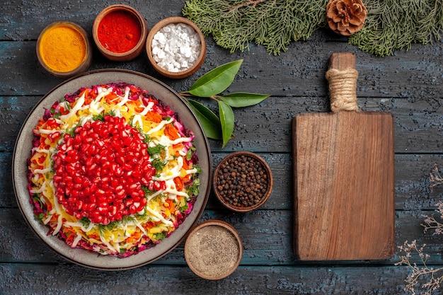 Draufsicht leckeres essen appetitliches weihnachtsessen und fünf schüsseln mit bunten gewürzen neben den fichtenzweigen aus holzküchenbrett mit zapfen
