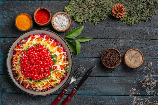 Draufsicht leckeres essen appetitliches weihnachtsessen und schüsseln mit gewürzen neben den gabelmesser-fichtenzweigen mit zapfen