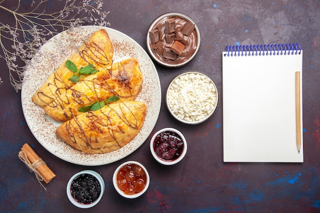 Draufsicht leckeres gebäck mit marmelade und hüttenkäse auf dunklem hintergrund gebäck süß backen tee kuchen zuckerplätzchen