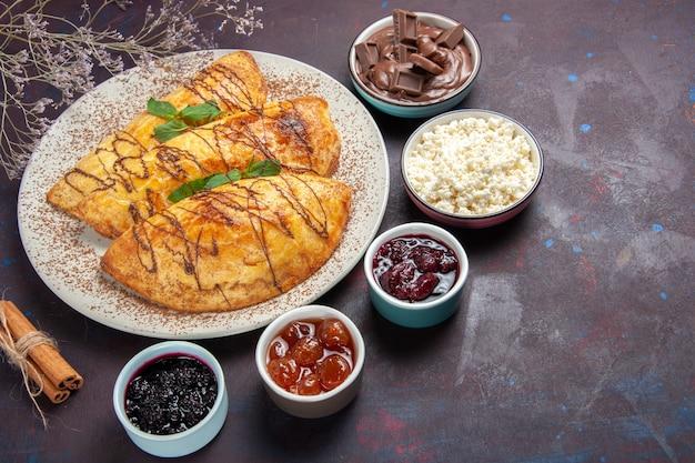 Draufsicht leckeres gebäck mit marmelade und hüttenkäse auf dunklem schreibtischgebäck süß backen tee kuchen zuckerkeks