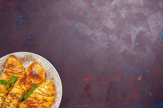 Draufsicht leckeres gebäck mit zuckerguss innerhalb platte auf dunklem hintergrund gebäck backen zuckerkeks süßer kuchen keks