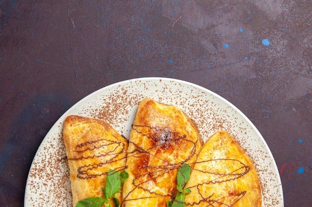 Draufsicht leckeres gebäck mit zuckerguss innerhalb platte auf dunklem schreibtischgebäck backen keks süßer kuchenzucker