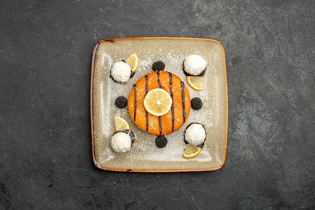 Draufsicht leckeres kuchendessert mit zitronenscheiben und kokosbonbons auf einer dunklen oberfläche desserttee süße kuchenkuchensüßigkeit