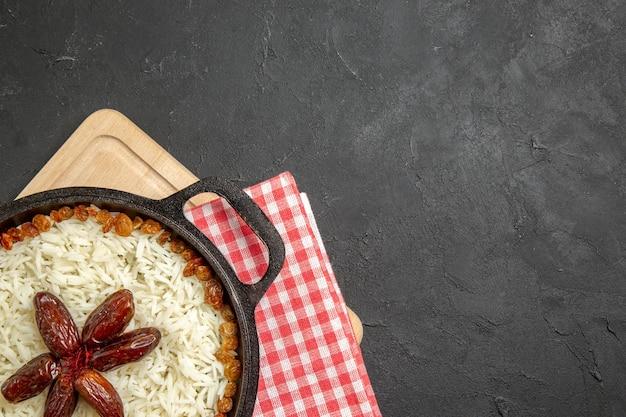 Draufsicht leckeres plov gekochtes reisgericht mit verschiedenen rosinen auf dem dunklen hintergrund