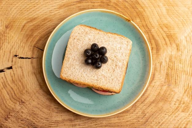 Draufsicht leckeres sandwich mit olivenschinken-tomatengemüse auf dem hölzernen hintergrundsandwich-nahrungsmittelsnack-frühstücksfoto