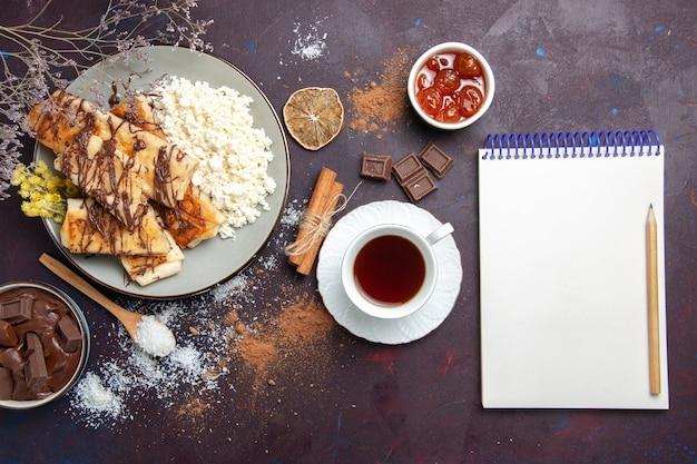 Draufsicht leckeres süßes gebäck geschnitten mit einer tasse tee und hüttenkäse auf einem dunklen schreibtischplätzchenplätzchenzuckersüßkuchengebäck