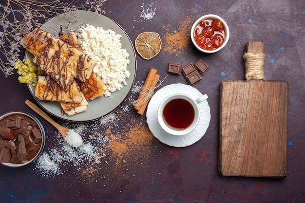 Draufsicht leckeres süßes gebäck geschnitten mit tasse tee und hüttenkäse auf dunklem hintergrund kekskekszucker süßes kuchengebäck