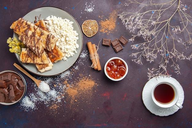 Draufsicht leckeres süßes gebäck geschnitten mit tee und hüttenkäse auf dunklem hintergrund kekskekszuckergebäck süßer kuchen
