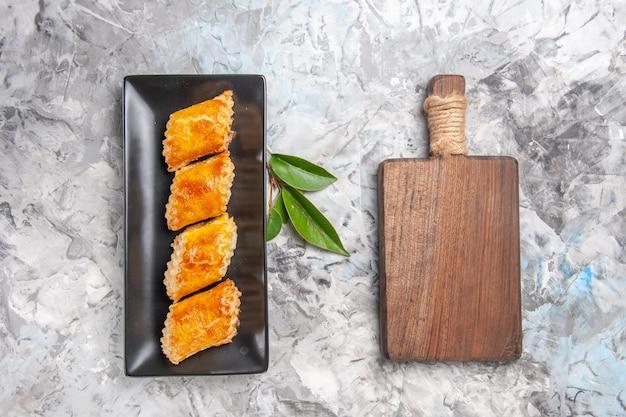 Draufsicht leckeres süßes gebäck in der kuchenform auf einem weißen süßen tortengebäckkuchen