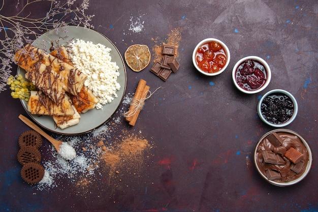 Draufsicht leckeres süßes gebäck mit hüttenkäse und marmelade auf dunklem hintergrundplätzchenkekszucker süßes kuchengebäck