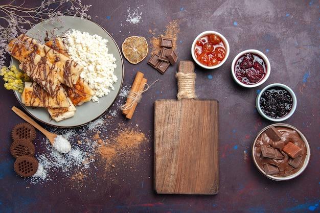 Draufsicht leckeres süßes gebäck mit hüttenkäse und marmelade auf dunklem schreibtischplätzchenkekszucker-süßem kuchengebäck