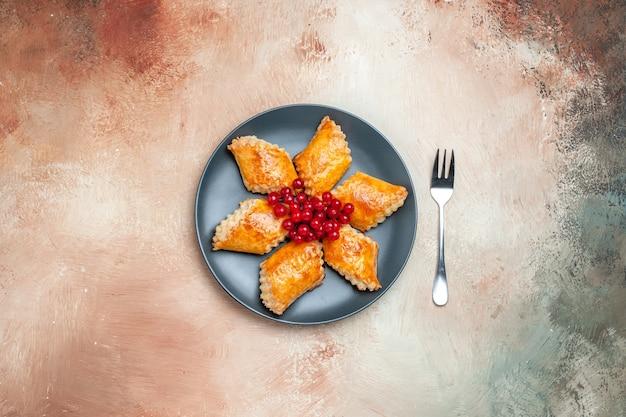 Draufsicht leckeres süßes gebäck mit roten beeren auf weißem tortenkuchen gebäck süß
