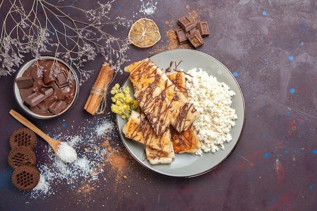 Draufsicht leckeres süßes gebäck mit schokolade und hüttenkäse auf dunklem hintergrund gebäckkekskuchenzuckersüßtee Kostenlose Fotos