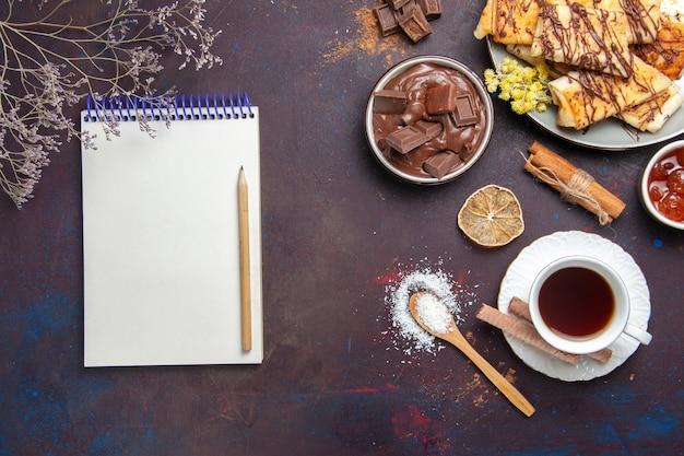 Draufsicht leckeres süßes gebäck mit tasse tee auf dunklem hintergrund gebäckkekskuchenzuckersüß