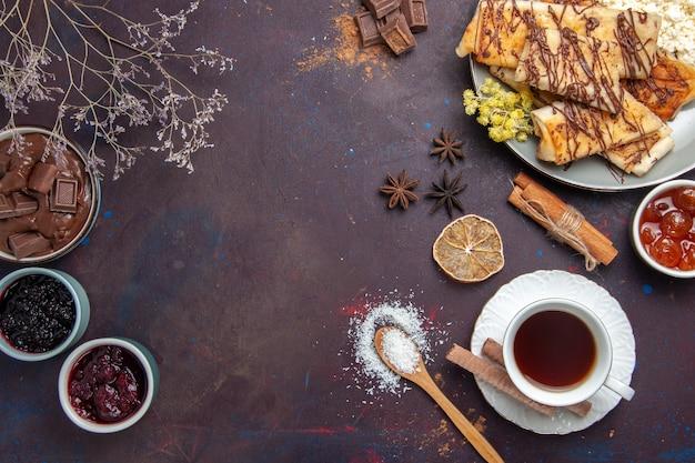 Draufsicht leckeres süßes gebäck mit tasse tee und marmelade auf dunklem hintergrund gebäckkekskuchenzuckersüßtee
