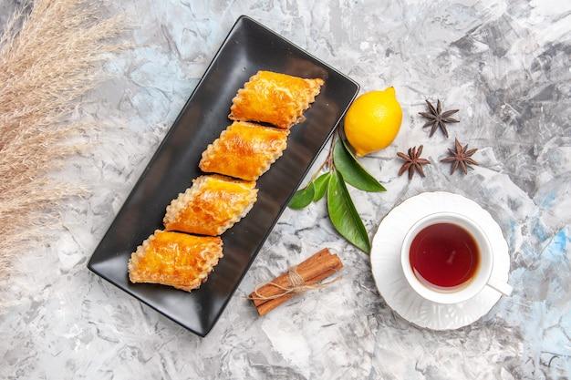 Draufsicht leckeres süßes gebäck mit tee auf weißem süßem tortengebäckkuchen