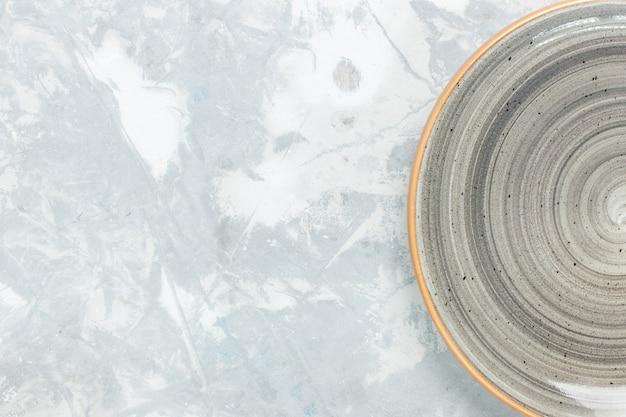 Draufsicht leere leere runde platte grau gefärbt auf weißer wandplatte küchenlebensmittelfoto besteck