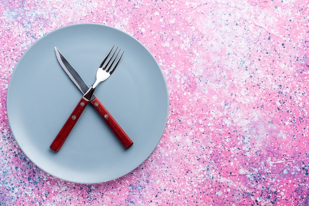 Draufsicht leere platte blau gefärbt mit gabel und messer auf der rosa wandfarbe fotoplatte lebensmittelbesteck