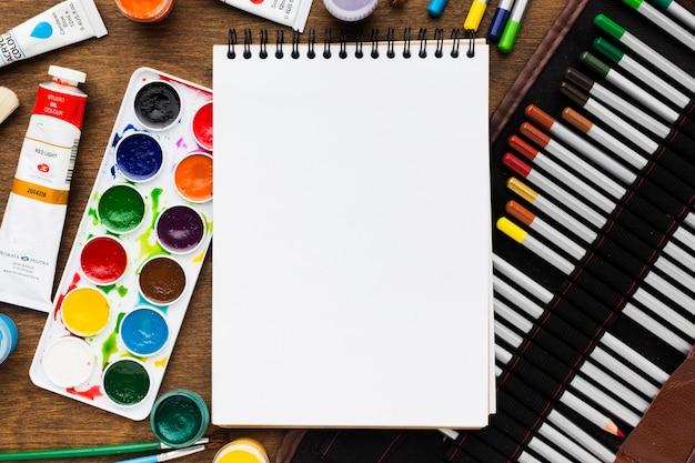 Draufsicht leerer notizblock, umgeben von farben