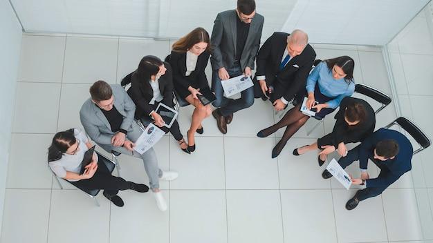 Draufsicht. leiter und geschäftsteam diskutieren arbeitsfragen. foto mit einer kopie des raumes