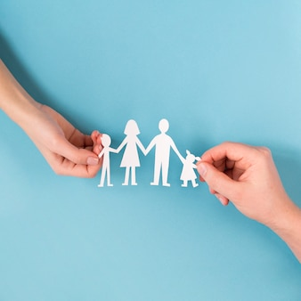 Draufsicht leute, die in händen niedliche papierfamilie halten