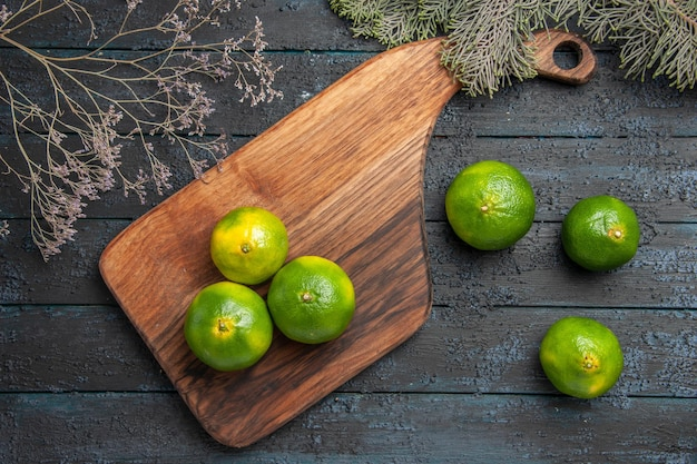 Draufsicht limetten an bord limetten auf schneidebrett auf dem tisch neben den ästen und drei limetten