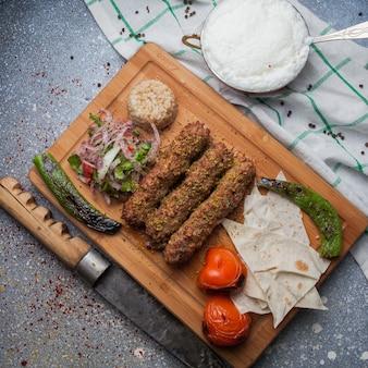Draufsicht lula kabab mit gebratenem gemüse und gehackten zwiebeln und messer und ayran im schneidebrett