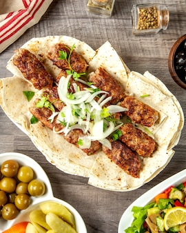 Draufsicht lula kebab auf fladenbrot mit zwiebeln und kräutern