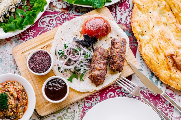 Draufsicht lula kebab auf fladenbrot mit zwiebeltomaten und saucen auf dem brett