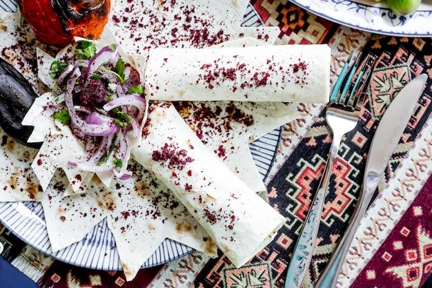 Draufsicht lula kebab in fladenbrot mit gemüse und zwiebeln mit sumach bestreut