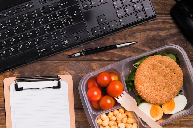 Draufsicht lunchbox und tastatur mit leerem notizbuch