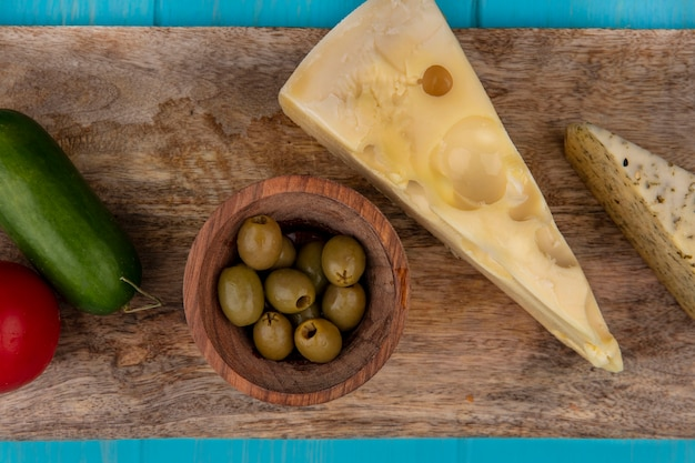 Draufsicht maasdam käse mit grünen oliven in schalen auf einem ständer und gurke mit tomate
